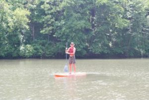 Midwest summer day enjoying paddle boarding at Camp Kupugani