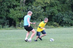 A group of campers kicking a soccer ball around the field