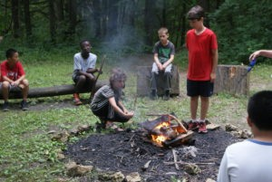 Boys enjoying making a campfire during outdoor living