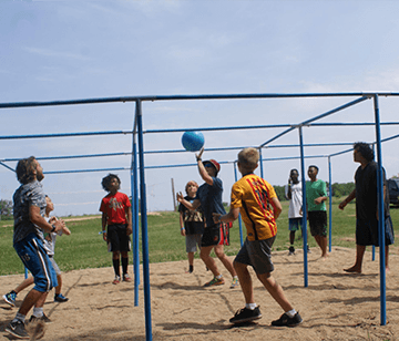 Imagine the playground game of 4-square meeting volleyball then played with 9 players at a time! The result is an incredibly fun, fast-paced and addicting game. We play it in the sand just south of our sand volleyball court. Kids and adults alike love this fast-paced game!