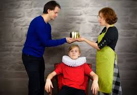 Parents putting a gold crown onto their childs head.