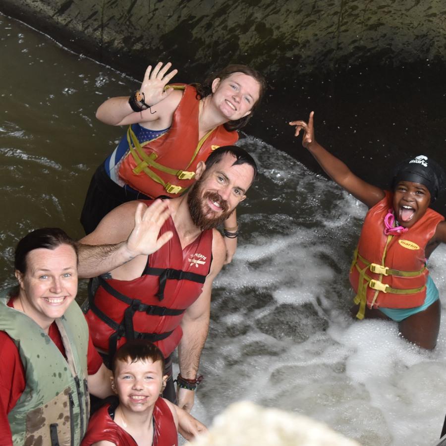 Campers having fun at the Leaf River Dam and Waterfall at Camp Kupugani